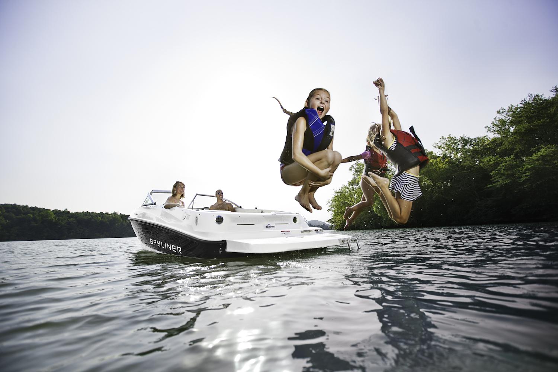 Kids jumping off the swim platform of a Bayliner sport boat