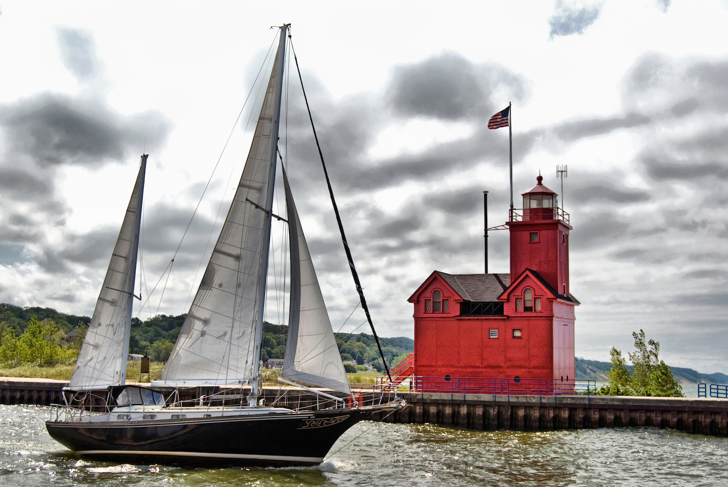 Sailboat sailing past a red lighthouse in Holland, Michigan.